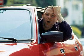 Mann im Auto ist genervt.