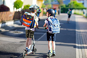 Jungs mit Roller auf dem Weg zur Schule