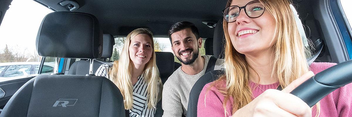 Ein paar sitzt auf der Rückbank im Auto einer Fahrerin