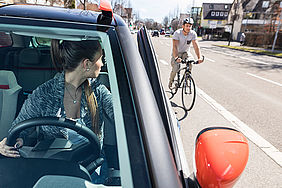 Autofahrende nimmt durch Schulterblick Rücksicht auf Radfahrenden.