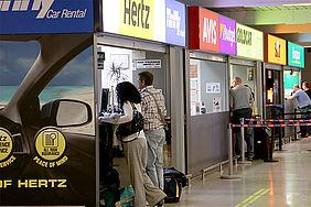 Mietwagenfirmen aneinander gereiht am Flughafen