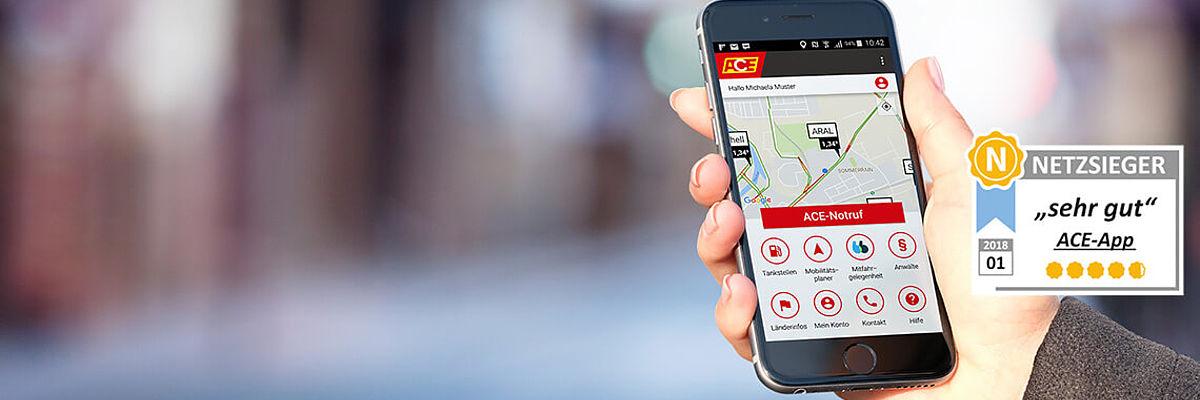 Hand hält Handy mit ACE-App und Testsiegel Netzsieger