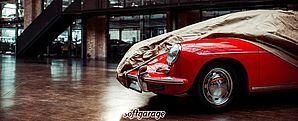 Ein roter Porsche steht halb abgedeckt mit einer Fahrzeuggarage von Softgarage in einer großen Halle
