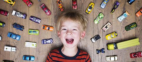 Lachendes Kind liegt auf dem Boden und um es herum Spielzeugautos