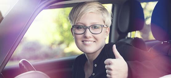 Junge Frau im Auto hebt Daumen hoch