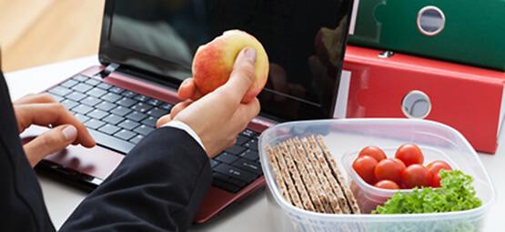Jemand ißt Obst und Gemüse am Laptop