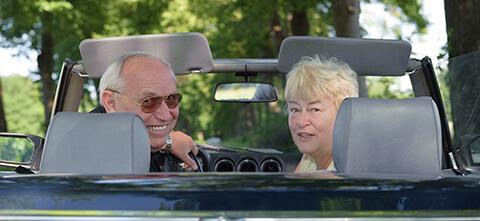 Rentnerehepaar sitzt im Cabrio