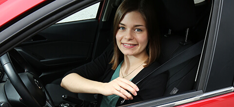 Frau sitzt im Auto und schnallt sich an