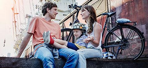 Paar mit Kind sitzt vor einem Fahrrad
