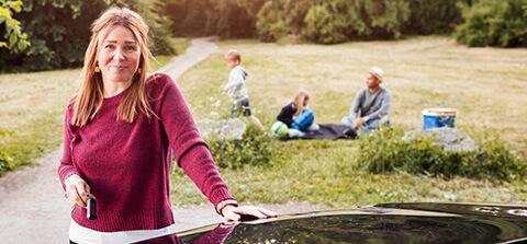 Frau im Vordergrund mit Familie im Hintergrund
