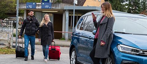Frau wartet auf Paar, die von der S-Bahn kommen, um diese mitzunehmen