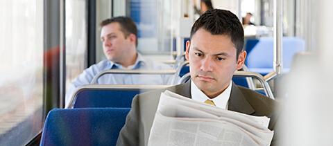 Mann sitzt in Bus und liest