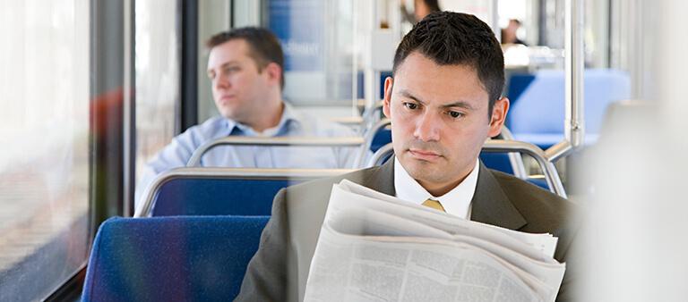 Mann sitzt im Bus und liest