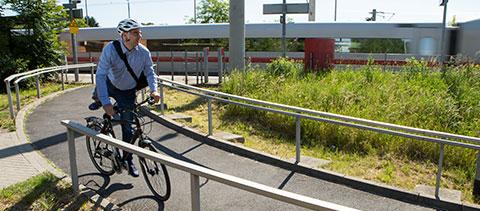 Mann auf dem Weg zur Arbeit steigt bei einer Bahn auf sein Fahrrad
