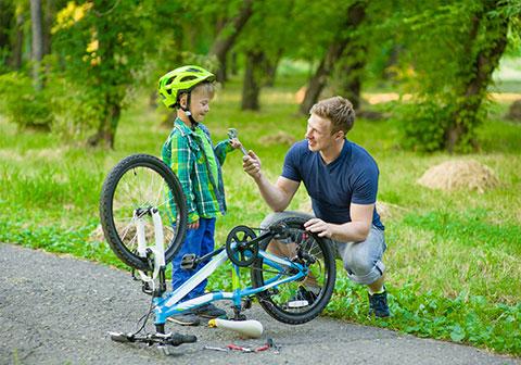 Vater repariert mit seinem Sohn ein Fahrrad