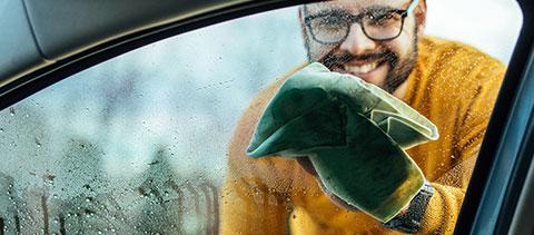 Mann reinigt eine Autoscheibe