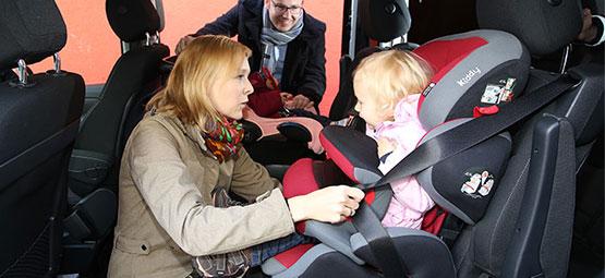 Mutter schnallt ihr Kind im Kindersitz an