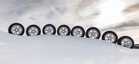 Eine Reihe Winterreifen steht im Schnee