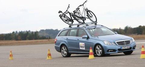 Auto mit Fahrradgepäcktrager auf dem Dach fährt Slalom
