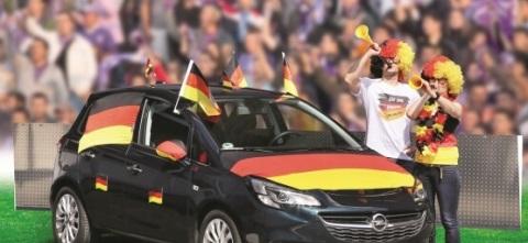 Jubelnde Fußballfans neben Auto.