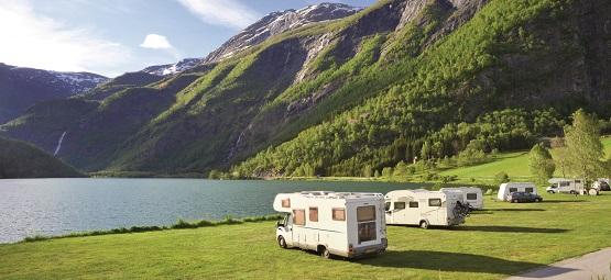 Campingwagen auf einem idyllischen Stellplatz am Wasser mit Bergen im Hintergrund