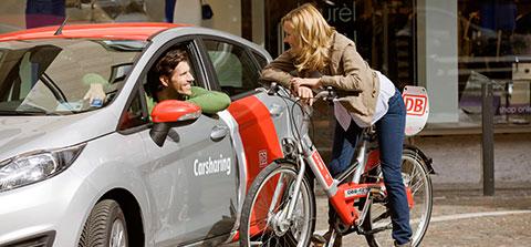 Frau auf Mietfahrrad unterhält sich mit einem Mann im Mietauto