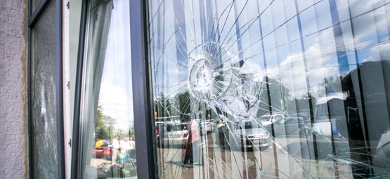 gebrochene Fensterscheibe eines Wohnhauses durch äußere Einlüsse
