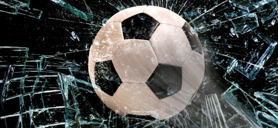 Fussball kracht durch eine Fensterscheibe