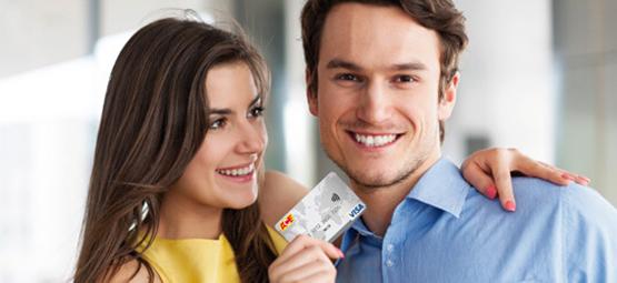 Junges Paar, die Frau hält eine ACE-Kreditkarte in der Hand und schaut den Mann lachend dabei an