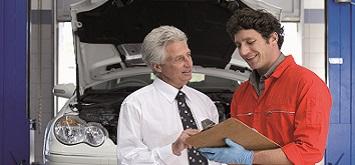 Ein Business Mann steht neben einem Mechaniker, der eine Checkliste in der Hand hält. Im Hintergrund ist das Fahrzeug mit offener Motorhaube zu sehen.
