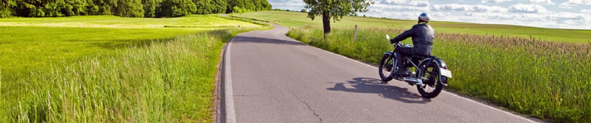 Ein Motorradfahrer fährt auf einer Landstraße mit einem Motorrad