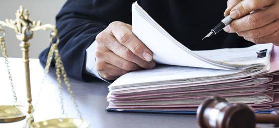 Ein Anwalt notiert etwas in seinem Ordner