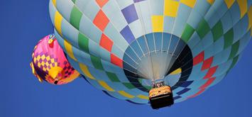 Ein Heißluftballon fliegt über ein Feld mit Blumen