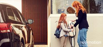Mutter und Kind stehen vor der NewMotion Ladesäule, daneben steht das Elektrofahrzeug