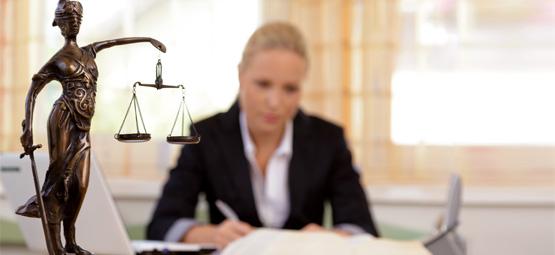 Justizia, im Hintergrund eine junge Anwältin