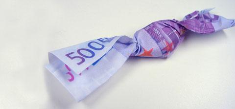 Ein Bonbon ist in einen 500 Euro Schein gewickelt