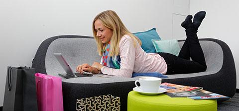 Frau liegt auf dem Sofa und kauft online ein