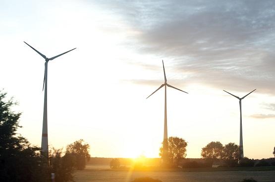 Windmühlen auf einem Feld bei Sonnenuntergang und blauem Himmel