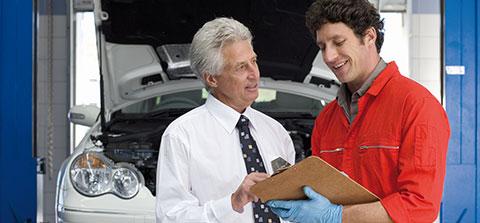 Zwei KFZ-Mechaniker checken ein Auto durch