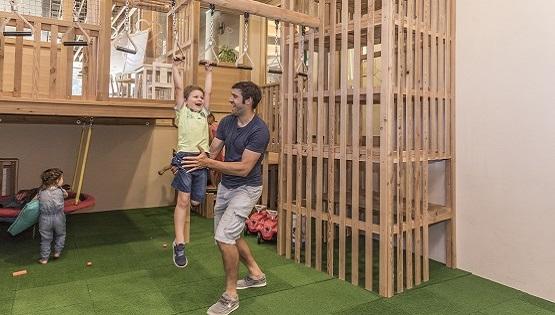 Indooraufnahme eines JUFA-Hotels, der Kinder und einen Erwachsenen auf einem Indoor-Spielplatz zeigt