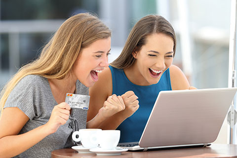 Zwei Frauen shoppen online per Kreditkarte