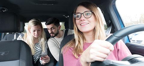 Eine Frau fährt Auto und nimmt zwei Mitfahrer mit