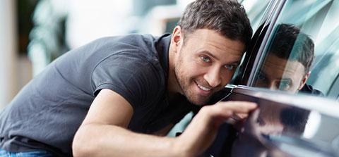 Mann untersucht einen Neuwagen