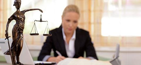 Justitia, im Hintegrund eine junge Anwältin