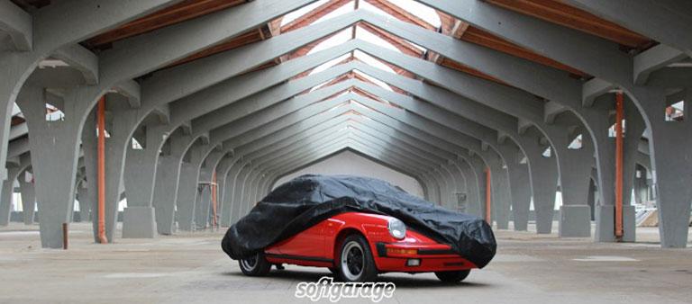 Ein halb abgedecktes Auto in einer großen Halle