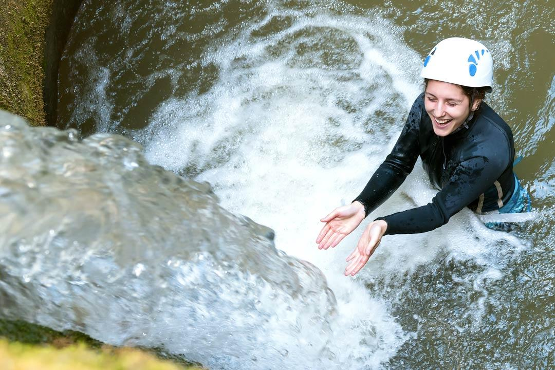 Happy woman wild water canyoning in Salzburg