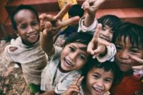 Kinder machen Peace-Zeichen in eine Kamera