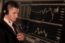 Junger Mann mit Kopfhörern schaut auf Aktienkurse